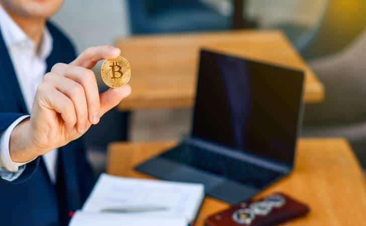 Homem-segura-uma-moeda-Bitcoin-para-apostar-online_ApostaBr
